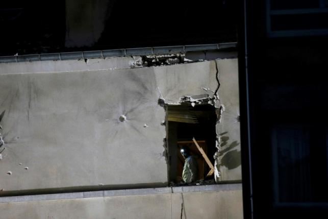 A forensic expert inspects the apartment raided by French Police special forces earlier in Saint-Denis, near Paris