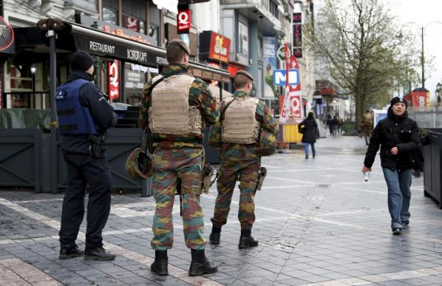 A Belgian police officer and soldiers patrol in a shopping area after security was tightened following the fatal attacks in Paris, in Brussels, Belgium