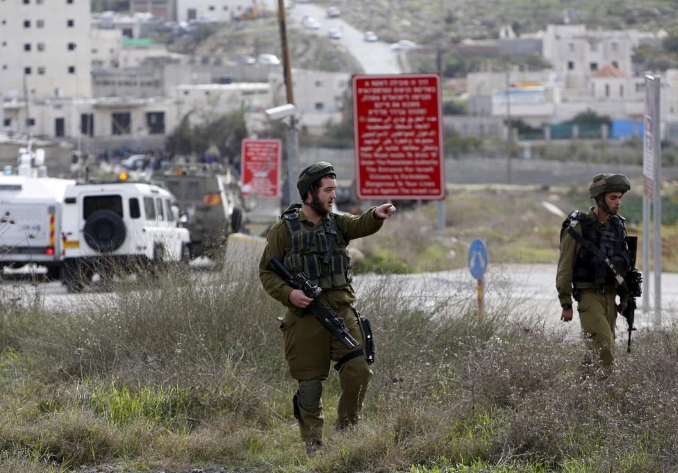 Israeli soldier gestures as he stands guard near the scene of what the Israeli army said was a suspected Palestinian stabbing attack, south of Hebron