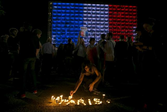 Israelis light candles during a ceremony honoring victims of the attacks in Paris, in Tel Aviv