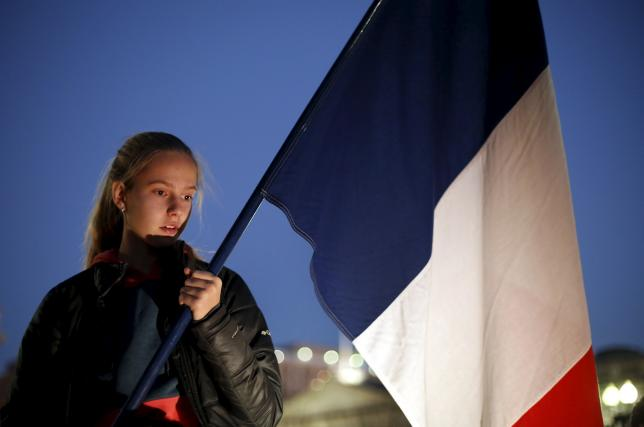 A girl holds a French flag during a vigil for the victims of the Paris attacks