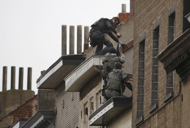 Belgian special forces police climb high on an apartment block during a raid in Brussels suburb of Molenbeek