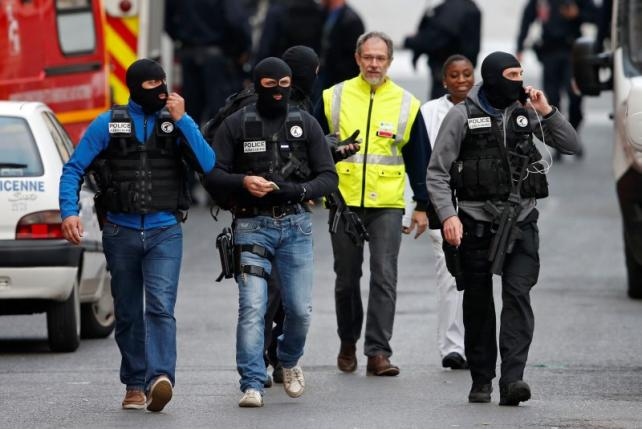 Masked French judicial police unit members walk at the scene of the raid in Saint-Denis