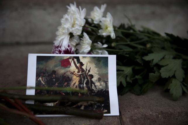 A postcard and flowers are left in tribute to victims of Paris attacks outside the French Embassy in London