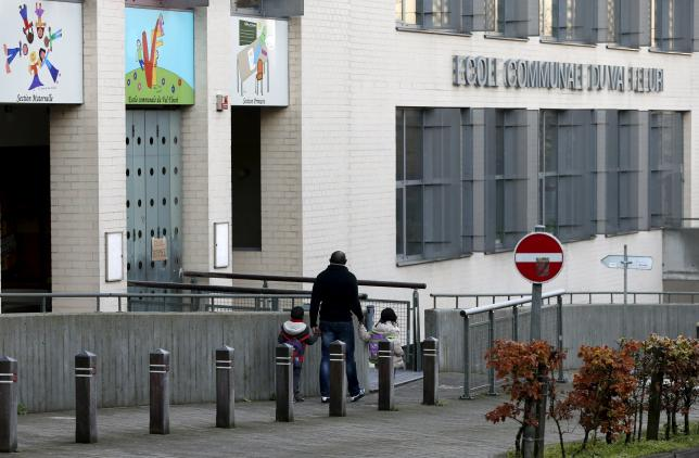 A man and his children stand in front of a closed primary and nursery school in Brussels