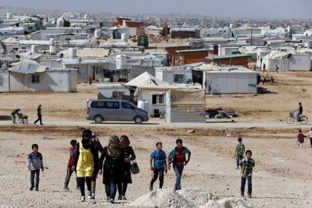 Syrian refugees walk at Al Zaatari refugee camp in the Jordanian city of Mafraq