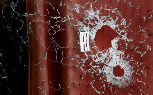 Bullet impacts are seen in the window of the Le Carillon restaurant the morning after a series of deadly attacks in Paris