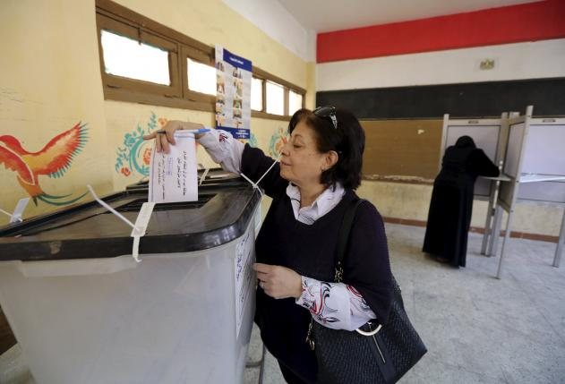 A woman casts her vote at a polling station during the second round of parliamentary elections at the Shubra area of Cairo, Egypt