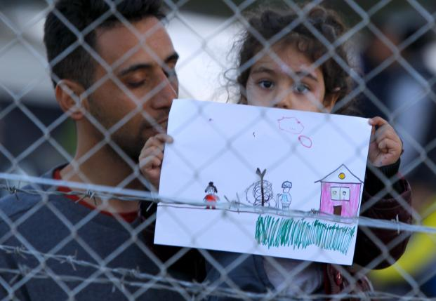 A young migrant girl holds up a drawing in makeshift camp on Macedonian-Greek border near Gevgelija
