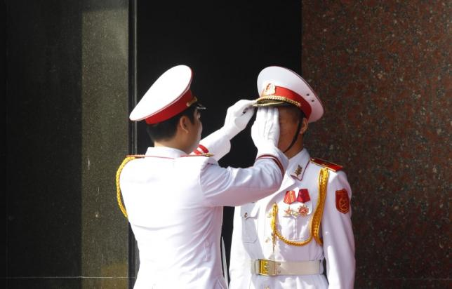Military officer adjusts the attire of an honour guard before a wreath-laying ceremony attended by China's President Xi Jinping at the mausoleum of late Vietnamese revolutionary leader Ho Chi Minh in Hanoi