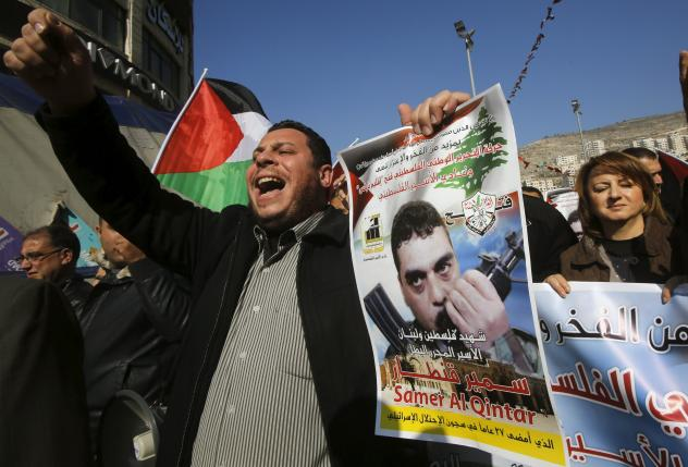 Palestinian man shouts slogans as he holds a poster of Qantar during a protest condemning Qantar killing, in Nablus
