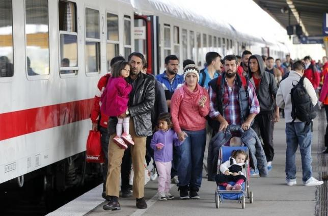 Migrants from Syria walk alomg a platform after arriving from Salzburg at Schoenefeld railway station in Berlin