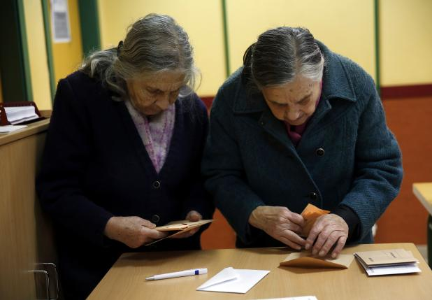 Voters prepare their ballots before voting in Spain's general election in Madrid