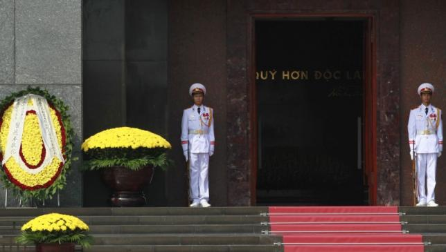Soldiers stand guard next to a wreath laid by China's President Xi Jinping after a wreath-laying ceremony at the mausoleum of late Vietnamese revolutionary leader Ho Chi Minh in Hanoi, Vietnam