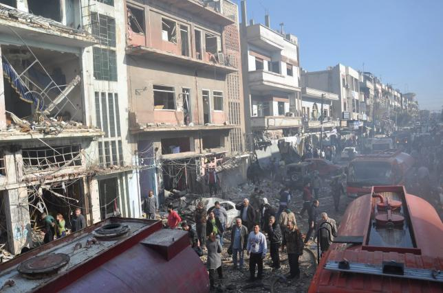 Syrian army soldiers and civilians inspect the site of two bomb explosions in the Syrian city of Homs