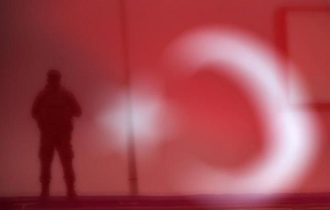 A soldier is seen through a Turkish national flag as he stands guard during an AK Party election rally in Diyarbakir