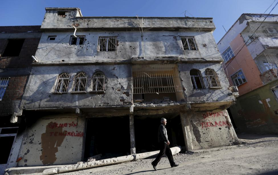 A man walks past a building which was damaged during the security operations and clashes between Turkish security forces and Kurdish militants, in the southeastern town of Silvan in Diyarbakir province, Turkey