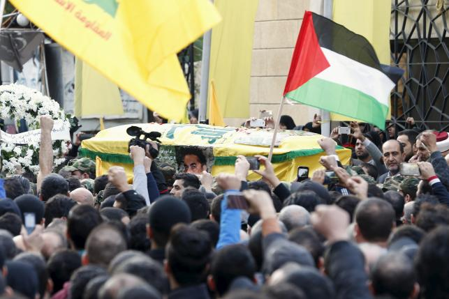 Hezbollah members carry the coffin of Lebanese Hezbollah militant leader Samir Qantar, as supporters carry Palestinian and Hezbollah flags during his funeral in Beirut's southern suburbs