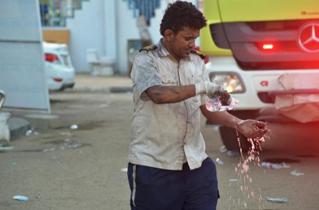 Man pours water onto his hand at Jazan General Hospital following a pre-dawn fire in the port city of Jazan