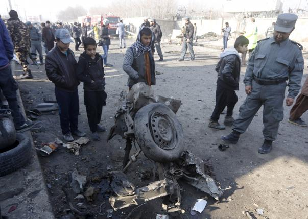 Afghan policeman and locals look at the wreckage of a car at the site of a suicide bomb attack in Kabul