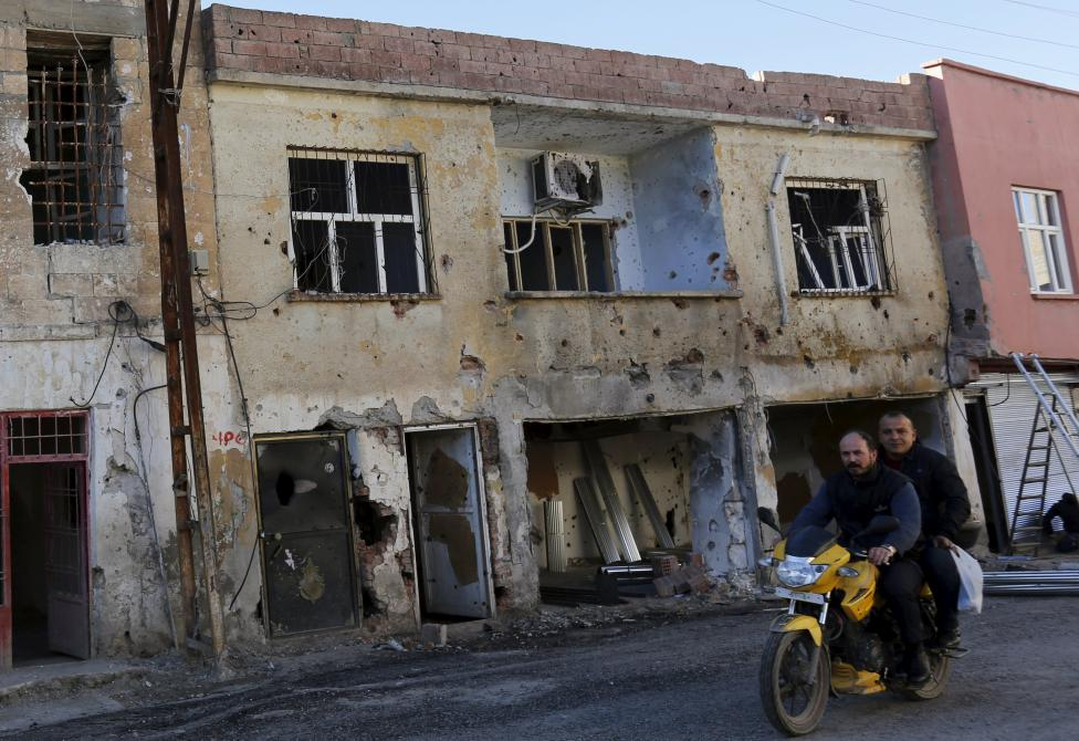 Men drive past a building which was damaged during the security operations and clashes between Turkish security forces and Kurdish militants, in the southeastern town of Silvan in Diyarbakir province, Turkey