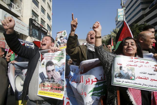Palestinians shout slogans as they hold posters of Qantar during a protest condemning Qantar killing, in Nablus