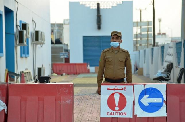 Member of Saudi security forces stands guard at Jazan General Hospital following a pre-dawn fire in the port city of Jazan