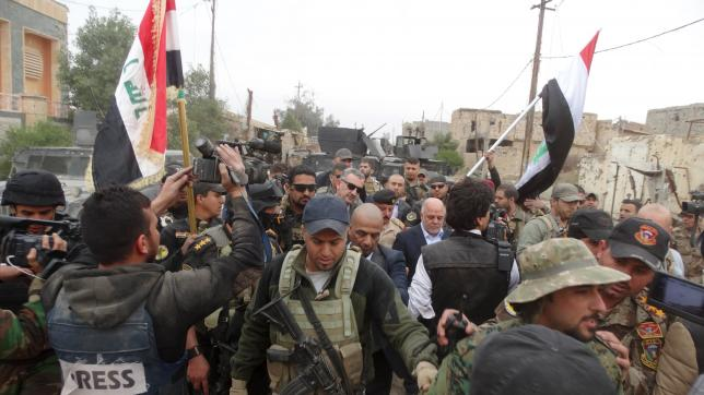 Iraqi Prime Minister Haider al-Abadi walks with his security detail in the city of Ramadi
