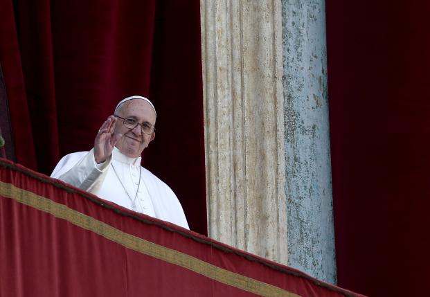 "Pope Francis waves during the ""Urbi et Orbi"" message from the balcony overlooking St. Peter's Square at the Vatican"