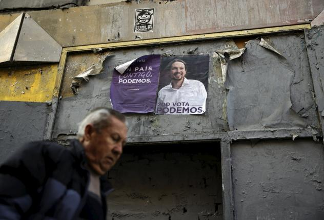 A man walks past posters of Podemos (We Can) party in central Madrid, Spain
