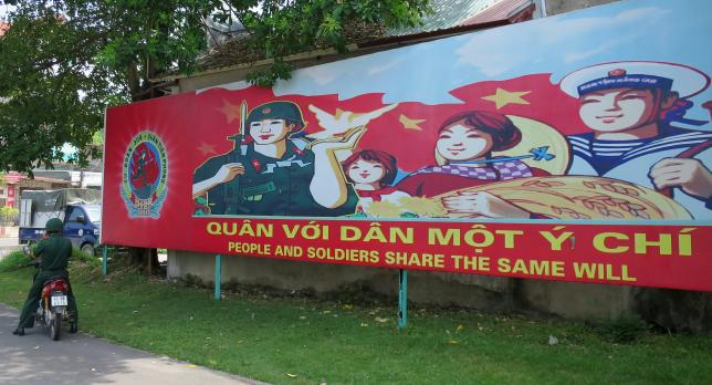 A soldier stands parks his motorcycle in front of a banner at the headquarters of the Division 308 special military force in Xuan Mai town, outside Hanoi