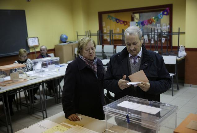 A man looks at his ballot before voting in Spain's general election in Madrid
