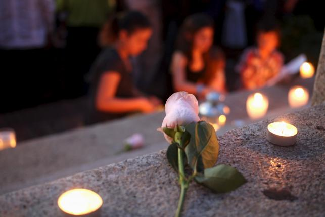 People light candles in tribute to the victims of Friday's Paris attacks, in Santo Domingo