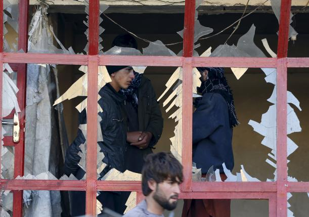 Afghans talks to each others inside their shop at the site of a suicide bomb attack in Kabul