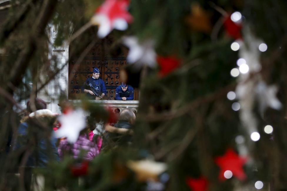 Belgian police officers are pictured through a Christmas tree as they patrol on Brussels' Grand Place