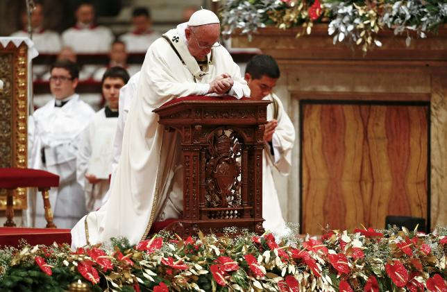 Pope Francis kneels as he leads the Christmas night Mass in Saint Peter's Basilica at the Vatican
