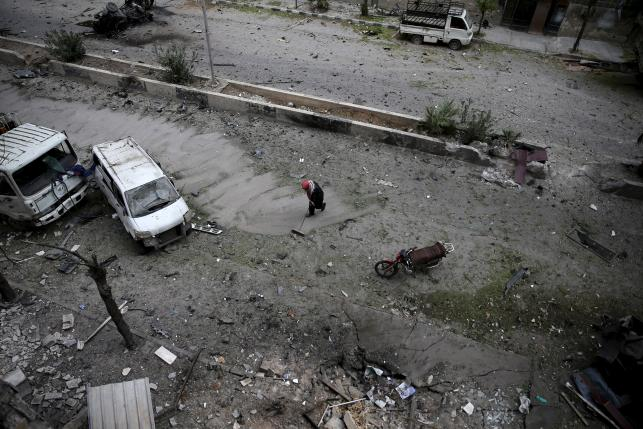 A man cleans up a damaged site after what activists said was shelling by forces loyal to Syria's President Bashar al-Assad in the Douma neighborhood of Damascus