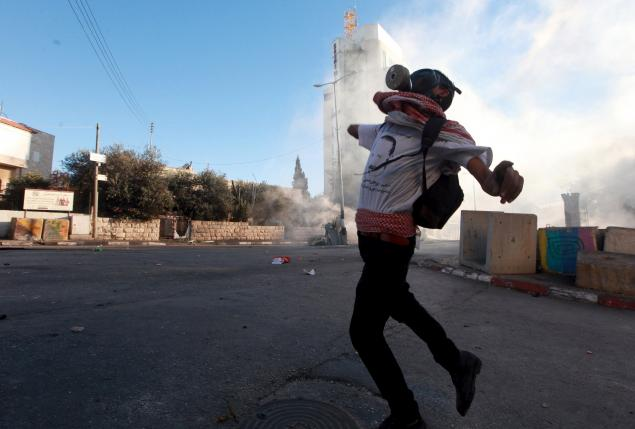 Palestinian protester hurls stones towards Israeli troops during clashes in Bethlehem