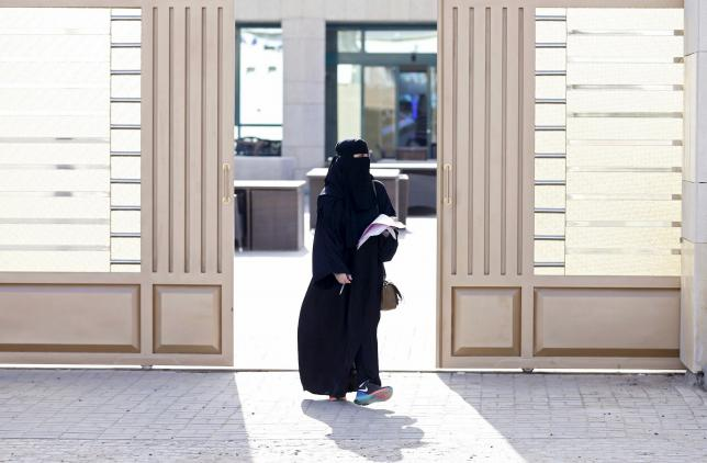 Woman leaves a polling station after casting her vote during municipal elections, in Riyadh, Saudi Arabia