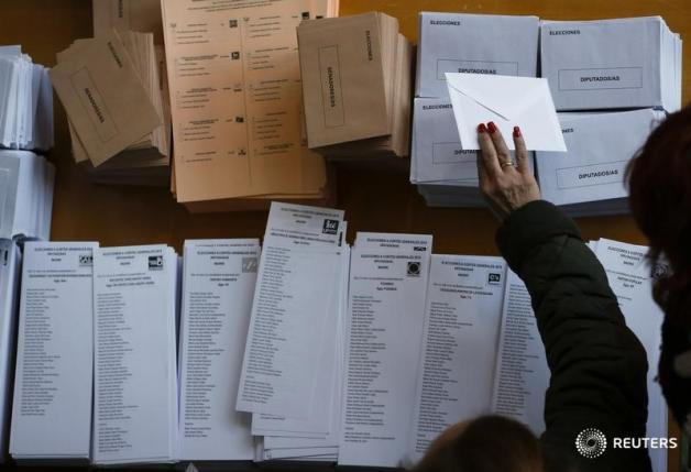 A voter reaches for a ballot envelope before voting in Spain's general election in Madrid
