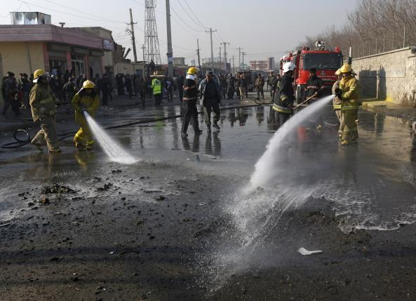 Fire-fighters spray water to clean the site of a suicide car bomb attack in Kabul, Afghanistan