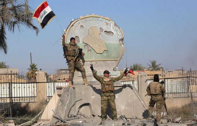 A member of the Iraqi security forces holds an Iraqi flag at a government complex in the city of Ramadi
