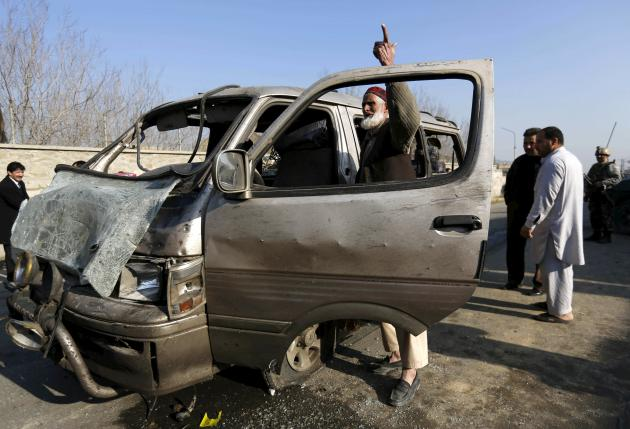 An Afghan man stands next to his damaged vehicle after a suicide attack in Kabul