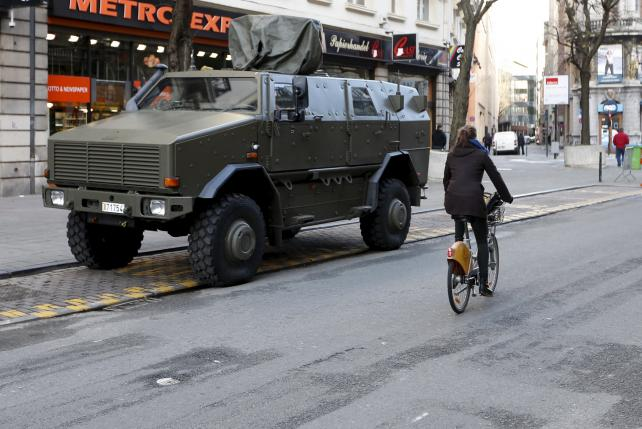A cyclist rides past a military armoured vehicle in central Brussels
