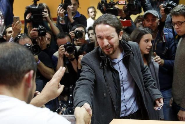 Podemos (We Can) party leader Pablo Iglesias greets polling workers while voting in Spain's general election in Madrid