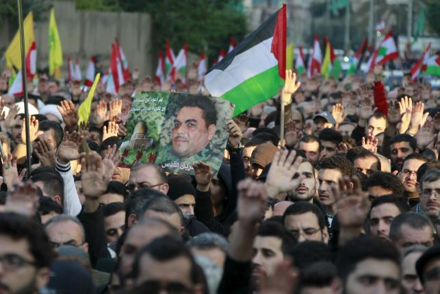 Relatives and supporters of Hezbollah militant leader Qantar carry a picture of him along with Lebanese, Palestinian and Hezbollah flags during his funeral in Beirut's southern suburbs