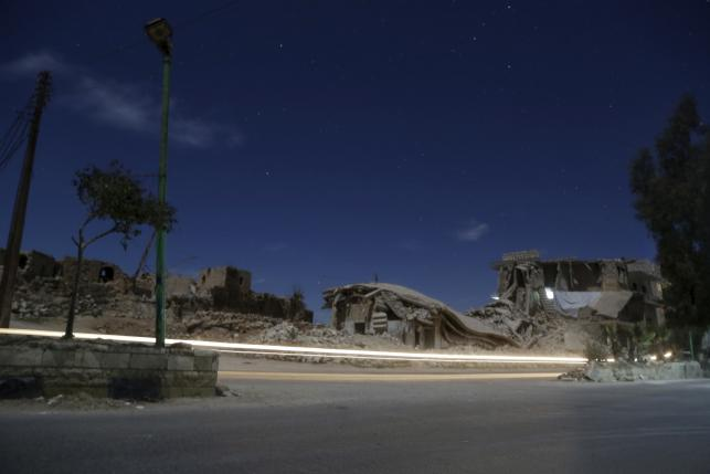 Damaged buildings are pictured at night in the rebel-controlled area of Maaret al-Numan town in Idlib province, Syria