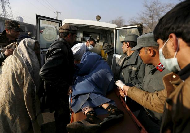 Police and relatives load an injured Afghan woman into an ambulance after she was wounded by a suicide attack in Kabul,