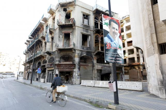 A man rides a bicycle past a poster depicting Syria's President Bashar al-Assad near the new clock square in the old city of Homs