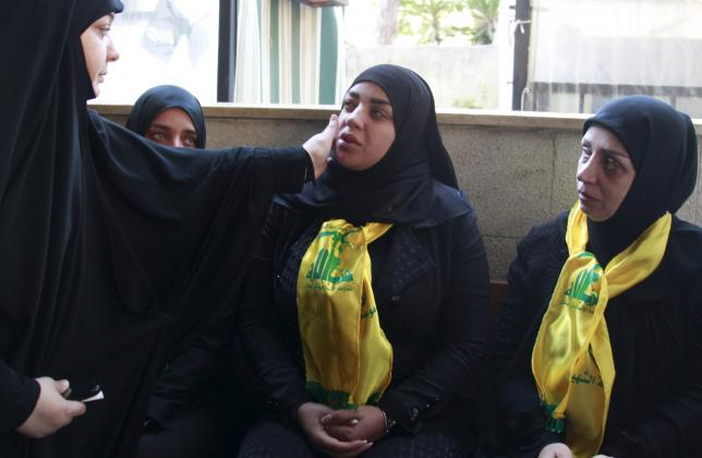 A woman comforts Zeinab Berjawi, the wife of Hezbollah militant leader Samir Qantar, during his funeral in Beirut's southern suburbs